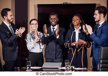 Equipo de negocios multiracial aplaudiendo en la sala de reuniones