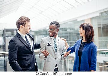 Equipo de negocios multiracial felicitaciones por el éxito de un colega afroamericano