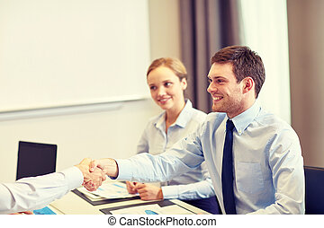 Equipo de negocios sonriente estrechando la mano en el cargo