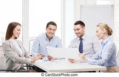 Equipo de negocios sonriente teniendo una discusión en la oficina