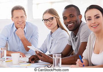 Equipo fuerte y creativo. Gente de negocios sentada en una fila en la mesa y sonriendo a la cámara