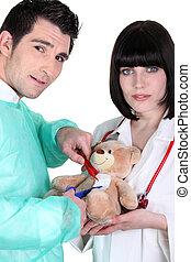 Equipo médico operando en un oso de peluche