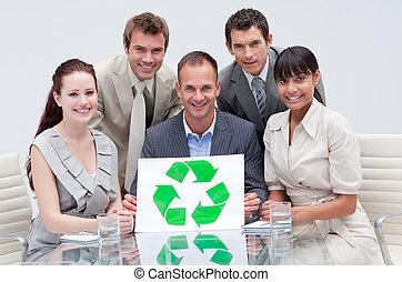 Equipos de negocios sonrientes sosteniendo un símbolo de reciclaje en la oficina. Negocios ecológicos