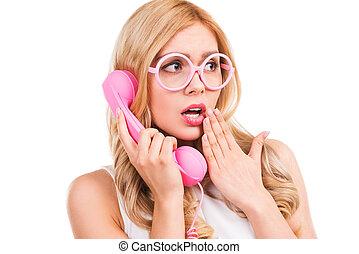 ¡Es increíble! Una joven rubia frustrada hablando por teléfono y cubriendo la boca con la mano mientras está aislada en el fondo blanco