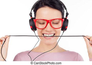 Es su canción favorita. Hermosa joven con gafas rojas y auriculares escuchando la música y manteniendo los ojos cerrados mientras está aislada en blanco