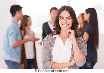 Es una líder de equipo. Una joven confiada sosteniendo la mano en la barbilla y sonriendo mientras un grupo de personas se comunican en el fondo