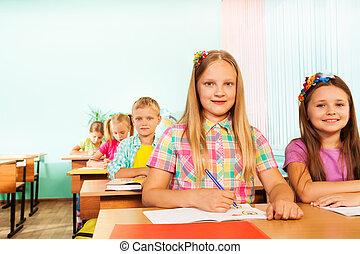 Escribir a una chica mirando fijamente y sentada en el escritorio