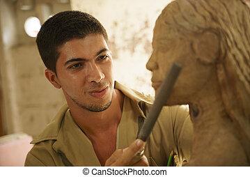 Escultor joven artista artesano trabajando esculpiendo esculturas