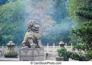 Escultura de león en la cerca del parque