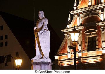 Escultura de roland en la plaza del ayuntamiento por la noche, riga, latvia