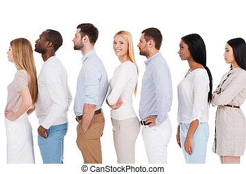 Esperando su turno. Una vista lateral de una hermosa joven mirando a la cámara y sonriendo mientras estaba de pie en una fila con otras personas y contra fondo blanco