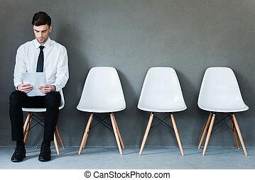 Esperando una entrevista. Confiado joven hombre de negocios sosteniendo papel mientras sentado en la silla contra el fondo gris