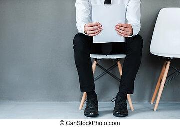 Esperando una entrevista. Un primer plano de un joven sosteniendo papel mientras se sienta en la silla contra el fondo gris