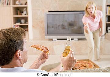 Esposa regañando a su marido por beber cerveza y comer pizza