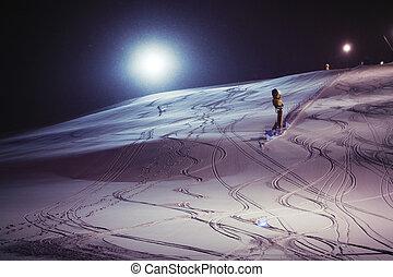Esquiar de noche en una noche nevada