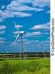 Estación de energía del viento, turbinas de viento contra el cielo azul y una hierba verde
