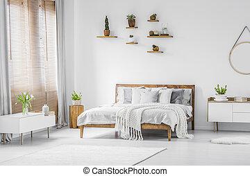 estanterías de madera con plantas sobre una cómoda cama doble en un espacioso interior de apartamentos con muebles blancos y paredes