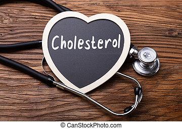 Estetoscopio y corazón con palabra colesterol