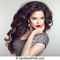 Estilo de pelo. Joyas de lujo. Retrato de modelo de belleza. Labios rojos. Cabello largo saludable. Mujer morena atractiva con maquillaje y uñas manicuradas.