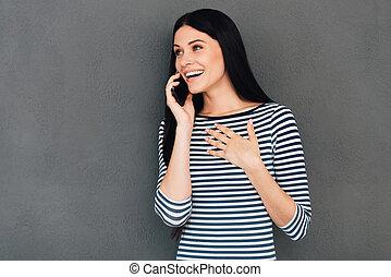 ¡Esto es increíble! Sorprendida mujer joven hablando por el teléfono móvil y sonriendo mientras se enfrenta a fondo gris