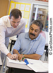 Estudiante adulto en clase con profesor ayudándolo