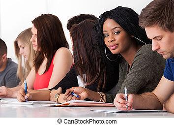 Estudiante confiado sentado con compañeros escribiendo en el escritorio