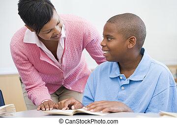 Estudiante en clase leyendo con profesor
