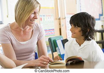 Estudiante en clase leyendo libros con profesor