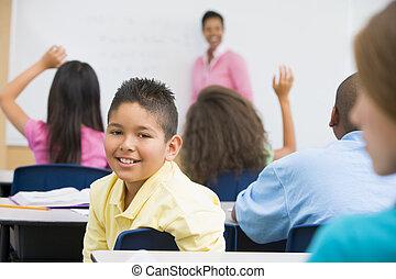 Estudiante en clase mirando cámara con profesor de fondo (centro selectivo)