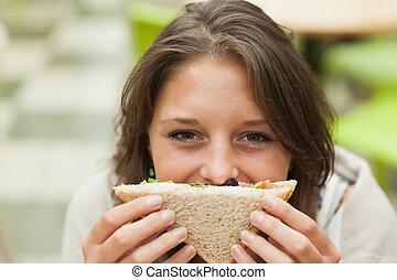 Estudiante femenina con sándwich en el