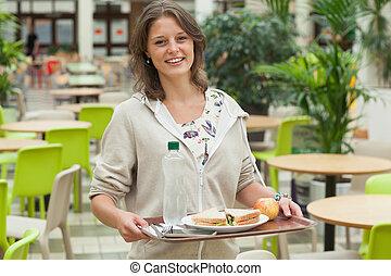 Estudiante llevando bandeja de comida en el