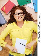 Estudiante sonriente con lápiz y libro de texto