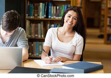 Estudiante sonriente escribiendo un papel