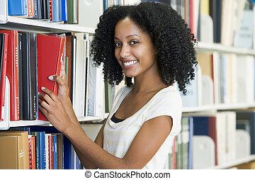Estudiante universitario seleccionando libros en la biblioteca