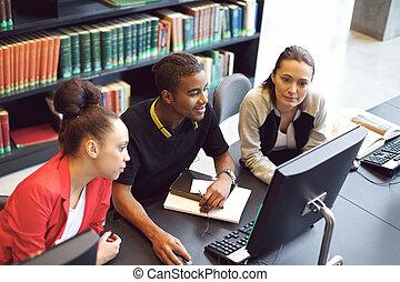 Estudiantes buscando información en la computadora para el proyecto escolar