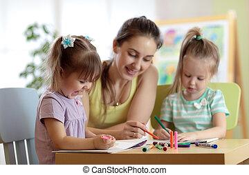 Estudiantes con maestros dibujando en la escuela de arte. Madre e hijos en casa. Los niños se lo permiten.