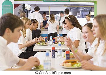 Estudiantes de secundaria comiendo en la cafetería de la escuela