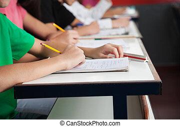 Estudiantes de secundaria escribiendo sobre papel en el escritorio