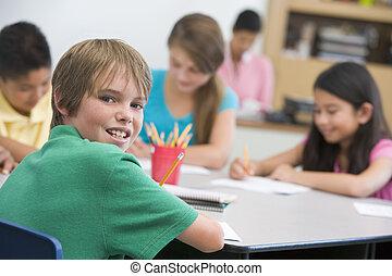 Estudiantes en clase escribiendo con profesor en el fondo (centro selectivo)