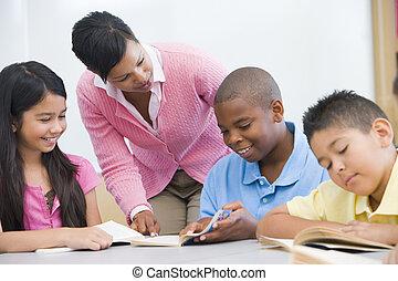 Estudiantes en clase leyendo con maestros ayudando (centro selectivo)