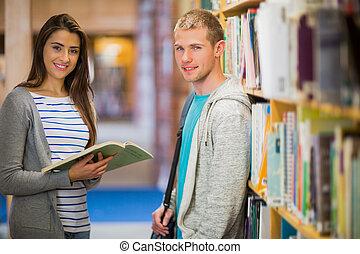 Estudiantes parados junto al estante de libros en la biblioteca