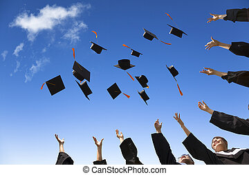 Estudiantes tirando sombreros de graduación en el aire celebrando