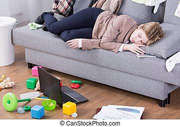 Exhausto después de todo el día de deberes maternales y oficinas