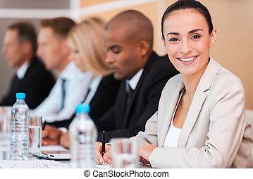 Experto en negocios confiado. Un grupo de gente de negocios sentada en fila y escribiendo algo en sus libretas mientras la hermosa joven de ropa formal mira a la cámara y sonríe