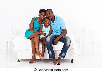 Familia africana sentada en la cama