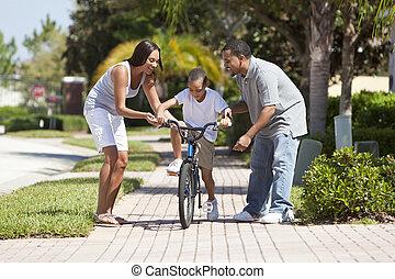 Familia afroamericana con niños en bicicleta y padres felices