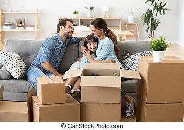 Familia atractiva sentada en la sala de estar en una nueva casa
