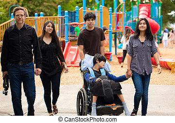 Familia caminando por el patio de juegos con el hijo discapacitado en silla de ruedas