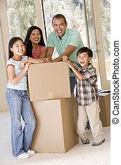 Familia con cajas en un nuevo hogar sonriendo