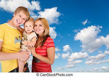 Familia con chico en blanco, nubes suaves en el cielo azul